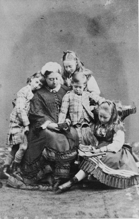 Queen Victoria com quatro de seus netos, o príncipe Albert Victor de Gales; Princesa Victoria de Hesse; Príncipe George de Gales (1865-1936); Princesa Elizabeth de Hesse (1864-1918) sentados juntos a ler livros em novembro de 1871.