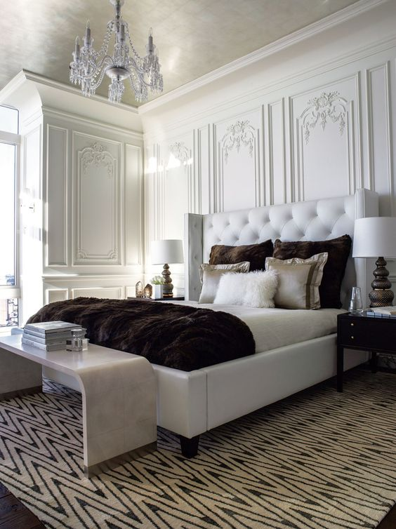 The master bedroom contrasts a modern white leather tufted bed with over-scaled faux fur pillows and throw; decorative painting and antiqued...: