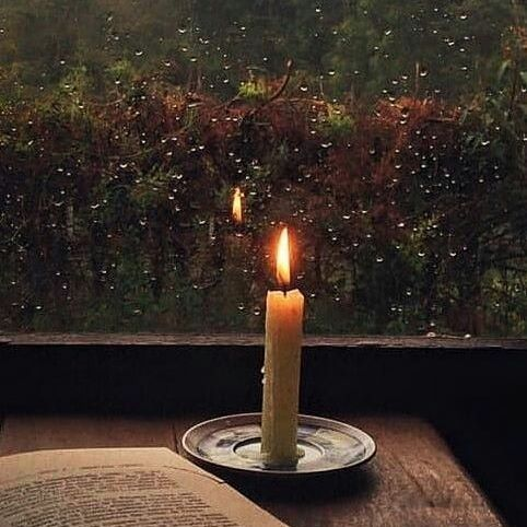 Inviting candle, good book and the rain OUTSIDE the window.