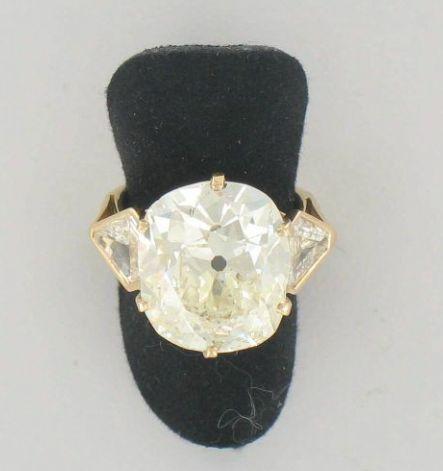 """Importante bague diamant solitaire  Elle est ornée d'un diamant de forme taille coussin en chaton à griffes et encadré par deux diamants """"fer de lance"""" en serti clos.  Monture en or jaune.  Poids brut : 7,5 gr.  Poids du diamant : 10,59 carats    A 10,59 carats diamond and gold ring."""