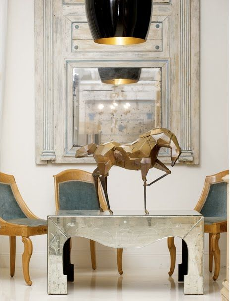 Bronze horse by Jaimie Acosta atop a mirrored mid-century coffee table with chinoiserie etching. In the background a Directoire French trumeau^, one of a rare pair. [^ a section of wall between two openings]: