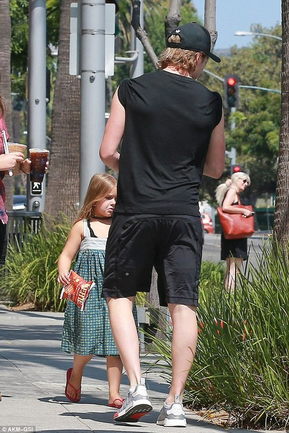 Harper Beckham enjoys a lollipop as dad David takes her out to eat
