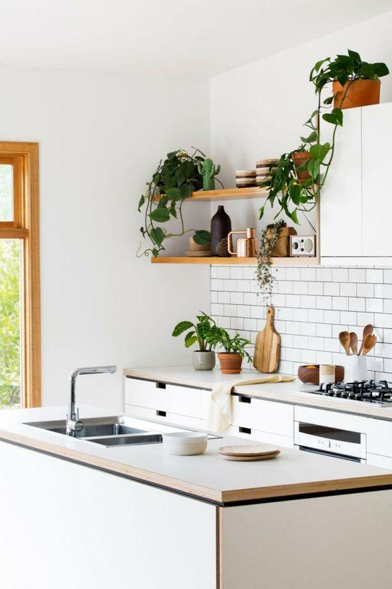 Witte keuken met houten accenten. de planten geven de keuken een ...