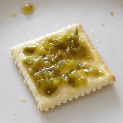 Mermelada de jalapeño. ¡Deliciosa! Yo tomo una barra de queso tipo filadelfia y lo baño en jalea de piña y sobre esto la mermelada de chile jalapeño. Luego se unta como dip sobre galletas Ritz. ¡Hay que probarlo para contarlo!