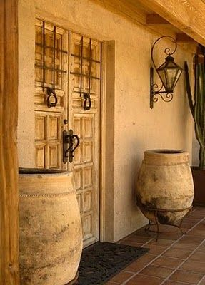 Mexico..beautiful entryway. Door hardware, pots and lighting of course. The scrollwork on the lighting fixture is ageless.