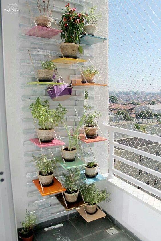 Horta vertical feita com estrado de madeira, cordas e prateleiras de madeira: