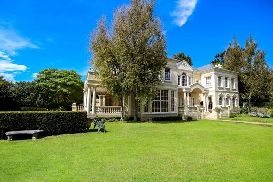 The+large+formal+dining+room,+of+this+French+style+home+in+Cape+Town+South+Africa+opens+unto+a+manicured,+private+garden+with+fountain.