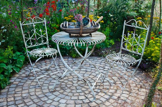 Classic circular cobblestone patio surrounded by garden http://www.uk-rattanfurniture.com/product/childrens-kids-red-rectangular-plastic-rope-swing-seat-hanging-outdoor-garden-mounting-bench-by-rope-swing/