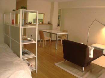 1Kインテリア事例2ベッドはダイニング側から丸見えにならないよう、間仕切りを兼ねて本棚を配置し、お手持ちのテーブルと椅子は、TELコーナーに利用。
