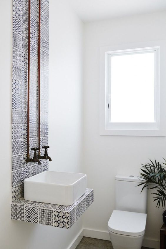 Stylish sink backdrop in this white bathroom.