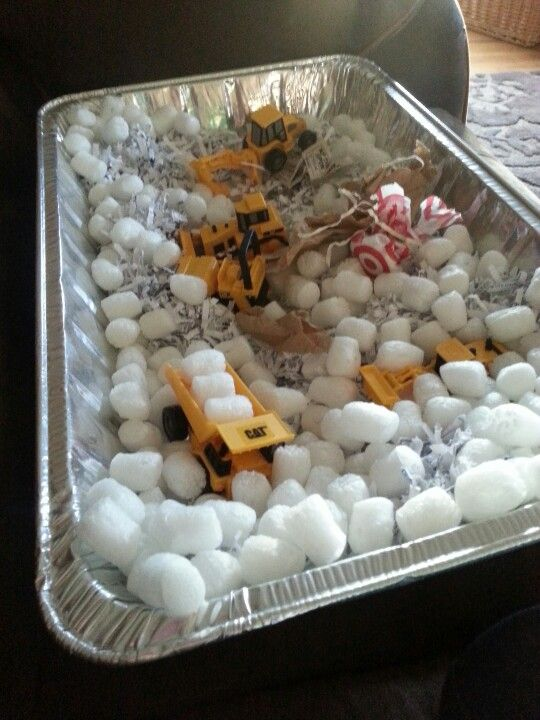 Instant fun.  Food tray.   Peanuts.  Shredded paper and construction vehicles.