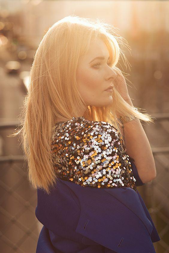 Model Christina Key steht im Gegenlicht und trägt ein goldenes Oberteil mit Pailletten