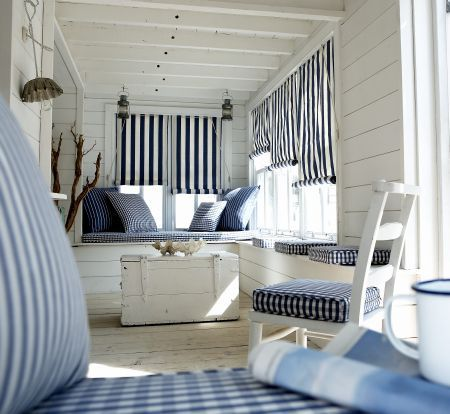 Prestigious Textiles -  Maritime Fabric Collection - Navy blue and white striped roman blinds, and navy blue and white chequered seating pads for a maritime house setting