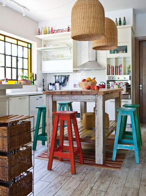 Cocina comedor rústica con aires vintage que combina función y belleza. Destacan la barra en madera bruta, grandes lámparas de mimbre y banquetas en rojo y turquesa.: