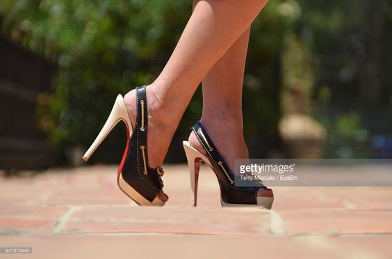 Stock Photo : Low Section Of Woman In High Heels While Walking On Street