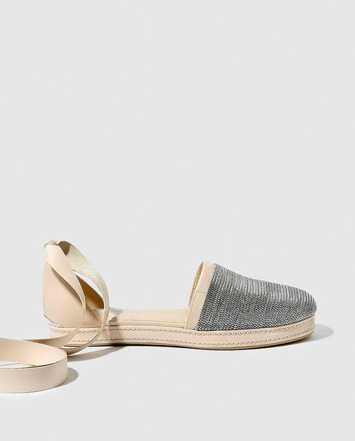 Sandalias planas de mujer Stuart Weitzman en color beige con adorno de cadena