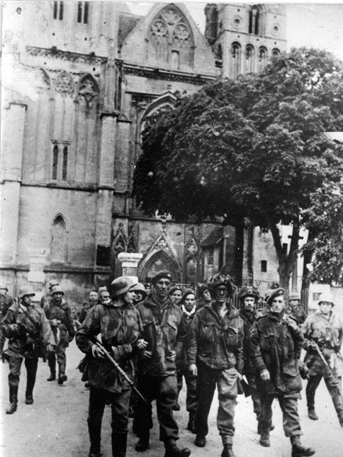 Colonne de parachutistes britanniques de la 6e Airborne division, faits prisonniers par des soldats allemands de la 21e Panzer Division, pris en photo devant l'église abbatiale de Saint-Pierre-sur-Dives, le 7 juin 1944. © US Army