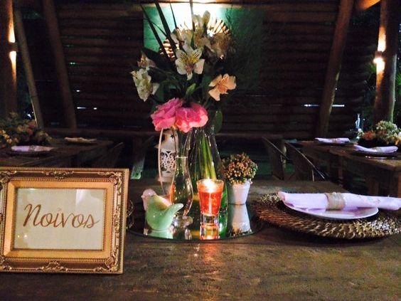 Arranjos pequenos e com velas...Discretos, que a realcem a decoração do lugar.