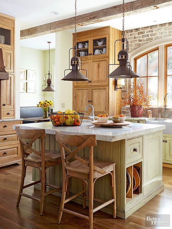 Rustic elements add layers of warmth that complement this kitchen's natural wood cabinetry and green glazed finishes.: