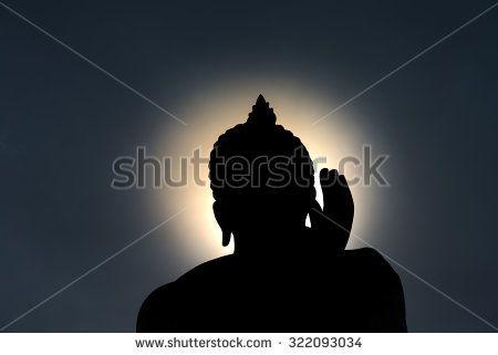 Buddha statue with dark silhouette and glowing golden light.NEF