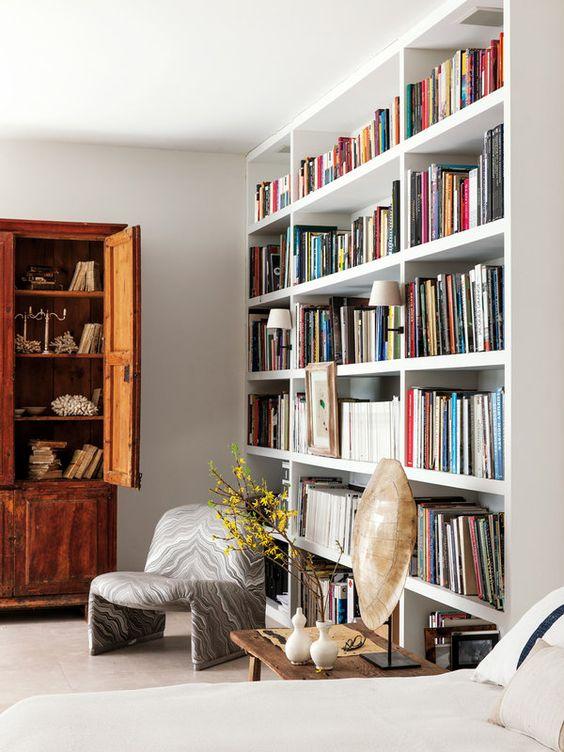 Librería lacada en blanco con apliques integrados, diseño del interiorista Luis Puerta. Al fondo, armario aragonés de madera del siglo XVII.