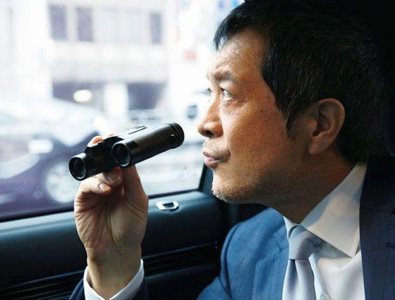 車に乗って小さい双眼鏡を持っている矢沢永吉の画像