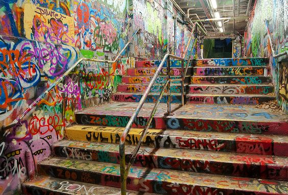 The Graffiti Tunnel at the University of Sydney, seen at night. A legal graffiti site for students of the university, colourful designs adorn the floor, walls and ceilings.