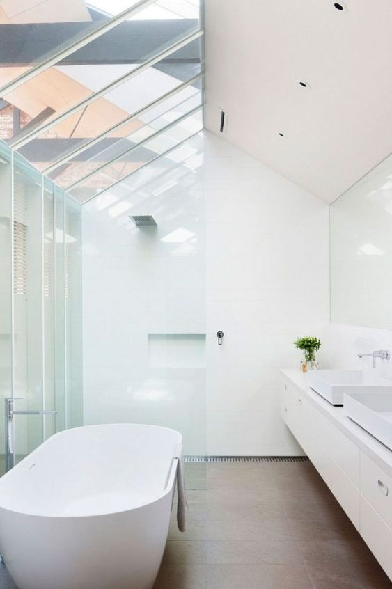 Contemporary bathroom in white with skylight and standalone bathtub