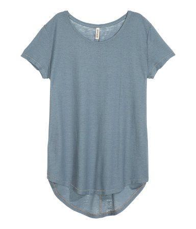 Top crêpé en jersey vaporeux. Modèle à manches courtes avec base arrondie et un peu plus de longueur dans le dos.