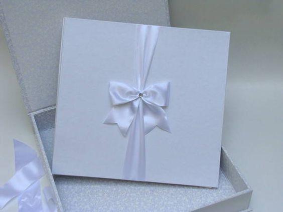 Conjunto de caixa e álbum para casamento.  Medidas: Caixa: 37,5x 36x6 encadernada com tecido Branco 100% algodão, detalhes em fita de cetim. Álbum: 34x32x3,5 encadernado com Papel metalizado Branco, detalhes em fita de cetim e chaton. Contem 10 plásticos,  também pode ser produzido com papel acid free.