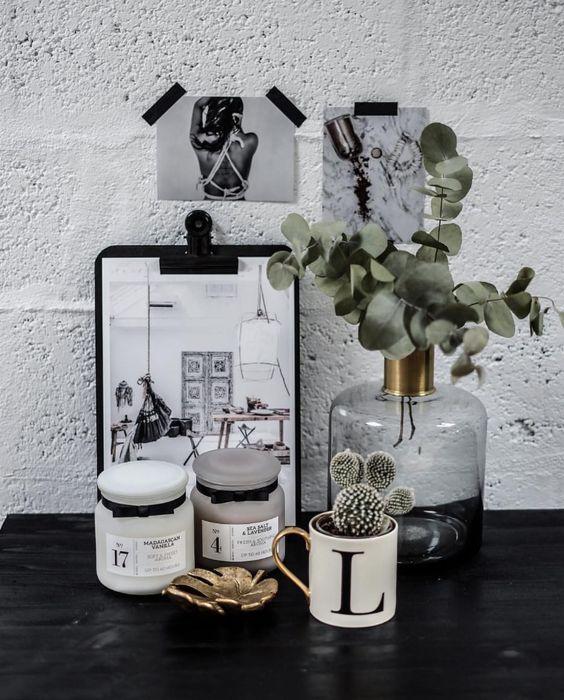 Flacon vintage bouteille en verre en laiton eucalyptus et cactus dans une décoration scandinave en noir et blanc.
