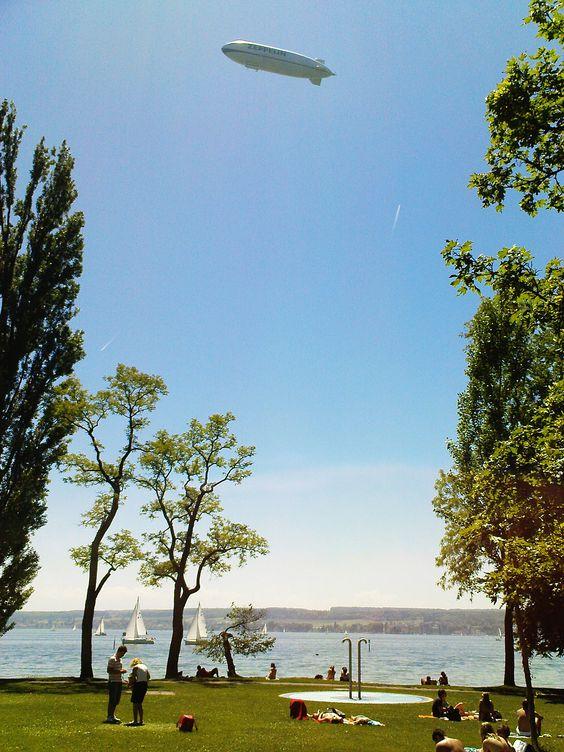 Ein Zeppelin über dem Freibad Horn in Konstanz. Da schaut man beim Sonnenbaden gerne auf zum Himmel. Ganz nah ist Friedrichshafen, die Heimat der Zeppeline (Ein Foto vom Profifotografen  Rudolf Warda)