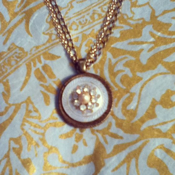 Simply Elegant. 1940's mother of pearl detailed button laid on a beautiful textured gold button. Decorated in vintage crystals and a vintage pearl.