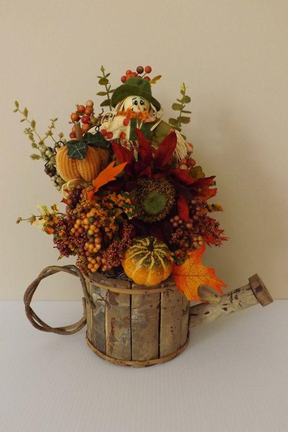 Fall floral arrangement in wooden watering can pumpkins