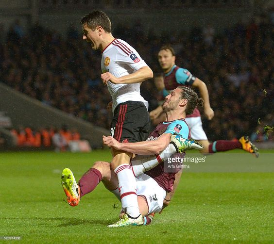 Andy Carroll of West Ham United in action with Ander Herrera of Manchester United during The Emirates FA Cup Sixth Round Replay at Boleyn Ground on April 13, 2016 in London, England.