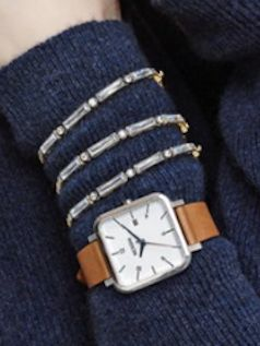 two tone baguette crystal bracelet paired with a square leather strap watch