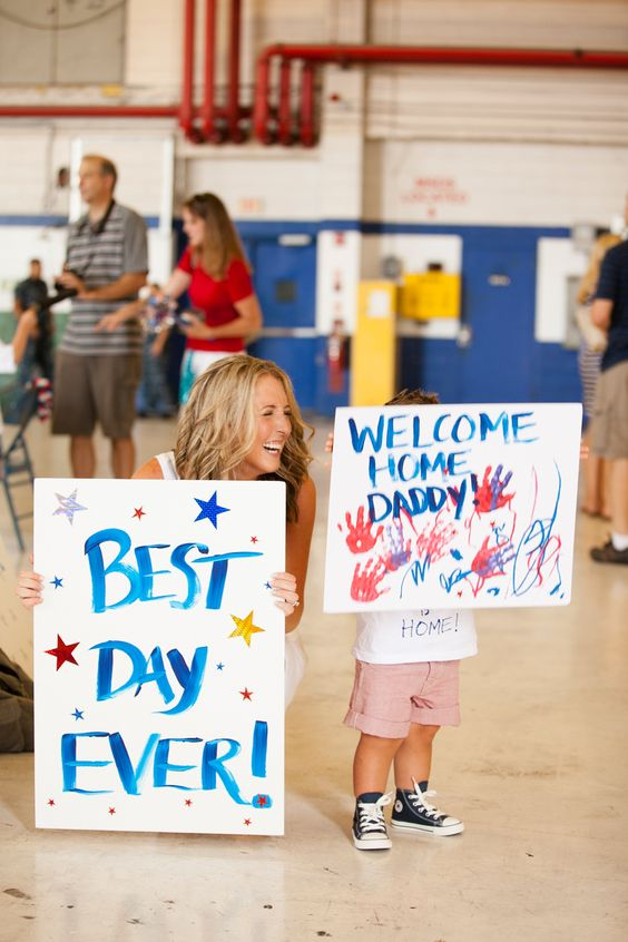 mom and son hold red white and blue signs that say best day ever and welcome home daddy by Tara Liebeck Photography