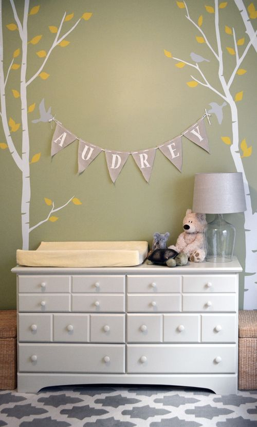 Gender-Neutral Nursery — Green Walls, White Birch Trees with Yellow Leaves — Wall Decals — Grey Birds — Hand Painted Stamped Burlap Baby Name Pennants — White Dresser Changing Station — Grey and White flat weave rug carpet — Shana Cunningham Designs www.shanacunningham.com