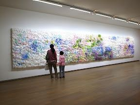 Mia Liu - This installation, entitled Can't Stop Rolling It Up, was originally a drawing that was enlarged onto 144 full sheets of watercolor paper and then cut and curled into strips and attached to an aluminum board.