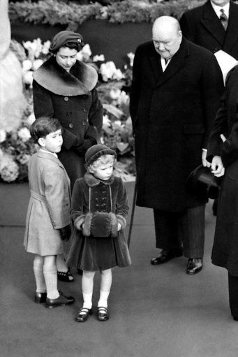 The Queen and Winston Churchill 24 Nov 1954.    Prime Minister Sir Winston Churchill beams down upon Princess Anne, her hands demurely folded in a velvet muff, as she waited with her mother, Queen Elizabeth II, and brother, Prince Charles, at Waterloo Station, London, to welcome home the Queen Mother from the tour of the United States and Canada.: