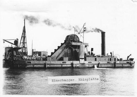 """Die Postkarte bildet den Dampfbetriebenen Eimerbagger """"Rhinplatte"""" ab, Baujahr 1916/26. Die Aufnahme stammt aus ca. dem Jahr 1920 bis 1930 und wurde im Jahr 2010 von der Bundesanstalt für Wasserbau als Postkartenmotiv verwendet."""