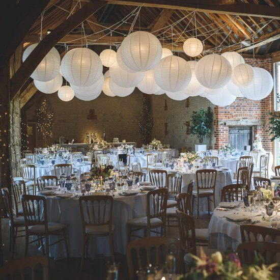 A romantic rustic barn reception full of hanging paper lanterns, pink florals and silver mercury glass votives & goblets.
