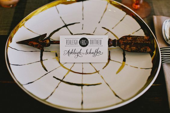 gold rimmed china plate with arrow decor // place cards