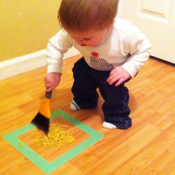 """Floor sweeping! We created a square out of painter's tape to help define the area to sweep into. Dried pasta or beans are perfect for this activity."":"