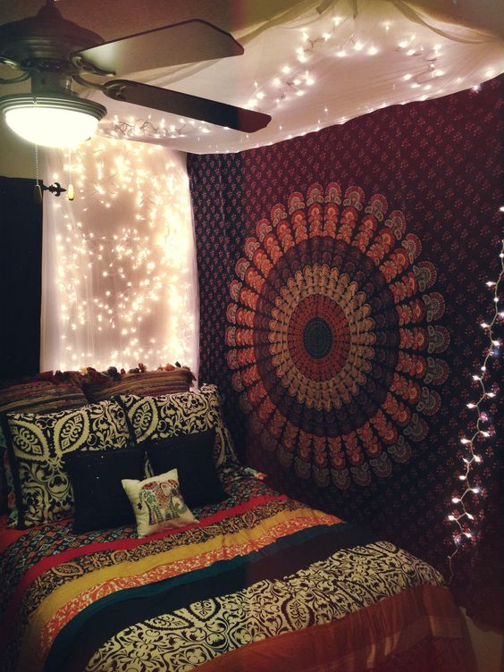 Anthropologie florence bedding, bed canopy with Christmas lights, and boho tapestry all in my college apartment bedroom