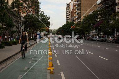 Córdoba, Argentina - 10 de abril de 2013: Un ciclista en su totalidad esta tarde nublada caminar a lo largo del carril bici en la avenida Hipolito Yrigoyen.Keywords: ciclista, nublado, tarde, caminando, en bicicleta, avenida, yrigoyen hipolito