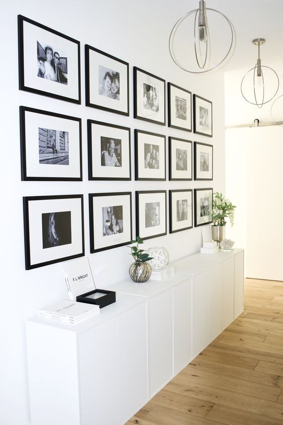 This hallway is right off the entrance of a beautiful modern Scandinavian apartment. A low bank of white Ikea Eket cabinets and a grid of black and white family photos create a carefully curated focal point for guests as they enter, and provides extra storage for small space living.   The symmetrical gallery wall, hung in a grid pattern goes almost floor to ceiling and strikes a balance between eye catching and minimal- exactly what these homeowners were aiming for in their apartment!