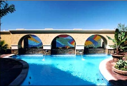 Three murals in an outdoor environment as the backdrop to a swimming pool in a multi-million dollar home