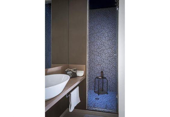 Linee pulite e design minimal per il piccolo bagno dell'appartamento lombardo ristrutturato da Studio76 Architetti a Osnago. Nel box doccia un mosaico azzurro e nero, mentre il mobile porta lavabo (su misura) riprende il grigio del soggiorno