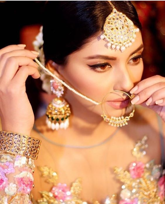bride putting on her gold and pearl nose ring matching her circular maang tikka and jumkas | Bride getting ready photos | Indian Wedding Ideas | Nose Rings | Indian Accessories | Bridal Look | Credits: Sunita marshal | Every Indian bride's Fav. Wedding E-magazine to read. Here for any marriage advice you need | www.wittyvows.com shares things no one tells brides, covers real weddings, ideas, inspirations, design trends and the right vendors, candid photographers etc.